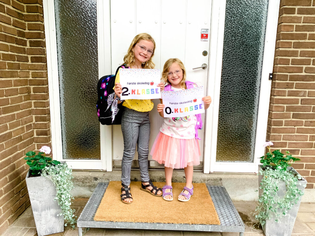 Skolepiger med første skoledag-skilt